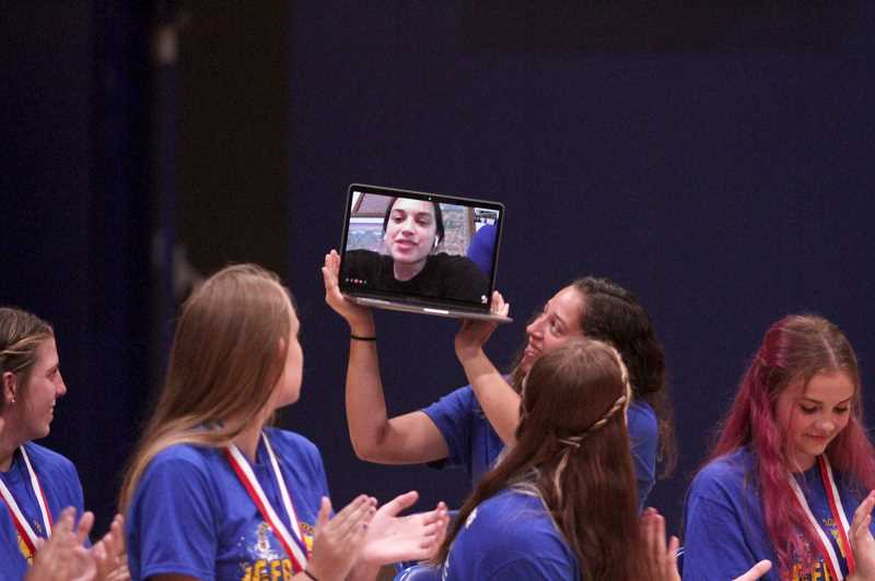 PMG PHOTO: PHIL HAWKINS - Sophomore guard Sofia Contreras was the lone member of the team unable to make it to the celebration in person, but she participated through video chat, held aloft by older sister and senior Isabel Contreras.