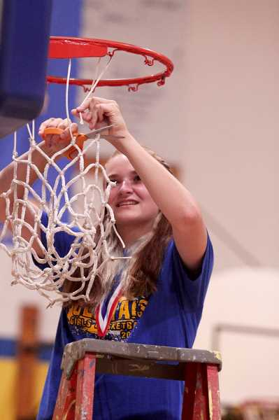 PMG PHOTO: PHIL HAWKINS - Sophomore Izzy Boyd cuts down one of the strings on the net to keep as a keepsake. All members of the team, including coaching staff, junior varsity members and the statistician took part in the net-cutting.
