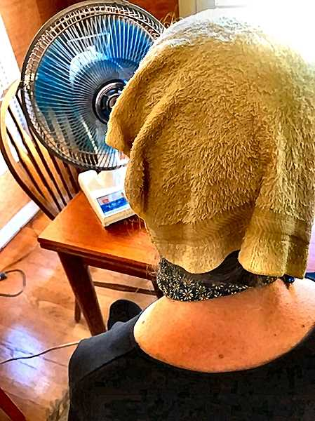 ELIZABETH USSHER GROFF - This person – one of many in Southeast who didn't have air conditioning – managed to survive the record heat wave with a cold wet wash cloth on the head, a cooling neck scarf, and a fan. Yes, there is somebody under there!