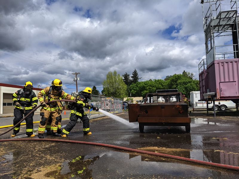 COURTESY PHOTO: JENN KING - Volunteers at Estacada Fire work together during a training simulation earlier this year.