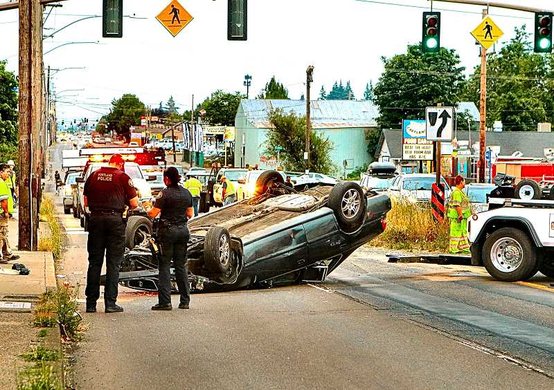 DAVID F. ASHTON - Traffic along S.E. 82nd Avenue of Roses came to a standstill when a rolled and smashed car came to a stop in the northbound lanes. Here, a tow truck was moving into position to remove it, using the southbound lanes.
