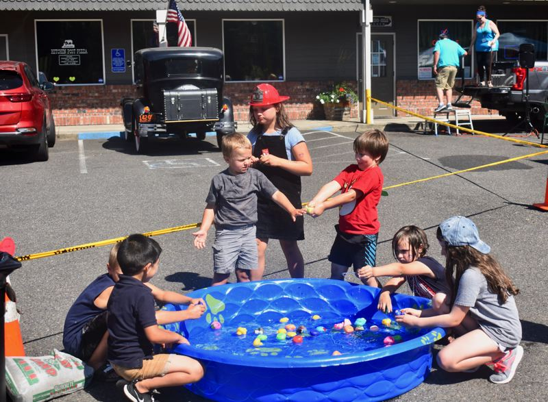 PMG PHOTO: EMILY LINDSTRAND - Children play in the water during a first responder appreciation event organized by Estacada Community Watch.