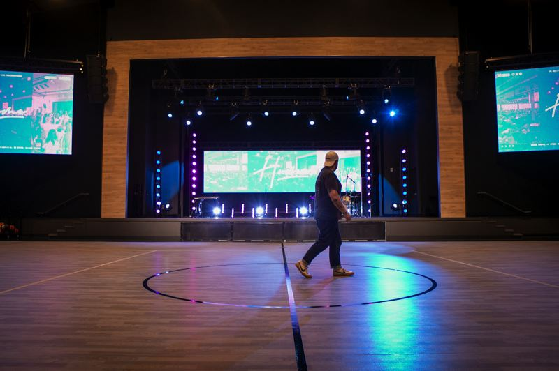 PMG PHOTO: JAIME VALDEZ - Jake Schwein, Grace Chapel's campus pastor and pastor of worship and justice, walks through the auditorium where church service is held. The space can also be used for sports like basketball.