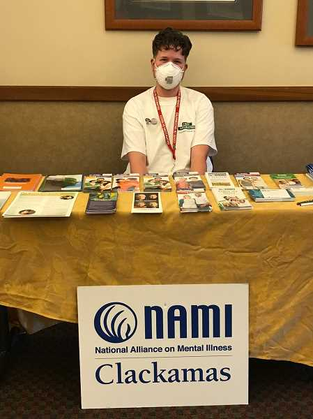 PMG PHOTO: LAURA CANIDA - Max Day, peer resource coordinator with NAMI Clackamas, answers questions and provides information to clients at the event.