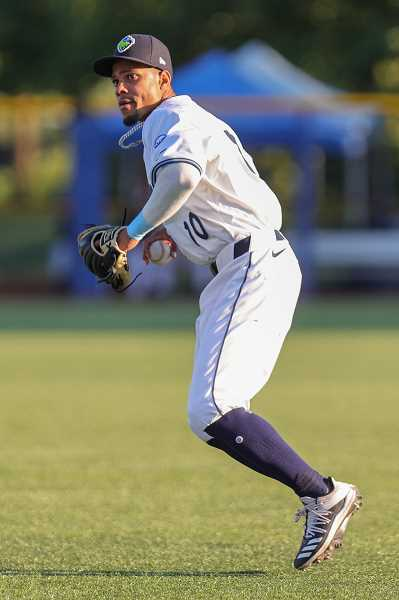 PMG PHOTO: JONATHAN VILLAGOMEZ - Hops outfielder Leodany Perez scoops up a ball and prepares to throw it in from the outfield during the Hillsboro's game against Vancouver Wednesday, July 14, at Ron Tonkin Field.