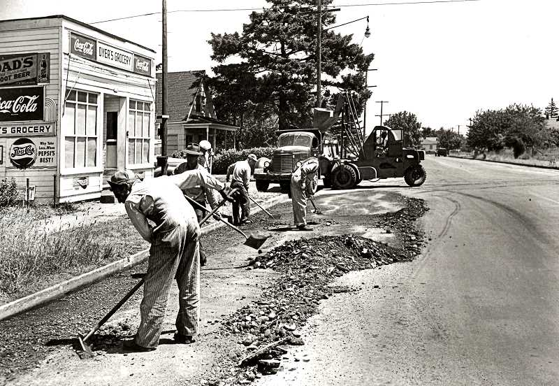 COURTESY OF PORTLAND CITY ARCHIVES - This photo, taken at 67th and S.E. Woodstock Boulevard in 1951, shows a road repair crew resurfacing a section of the boulevard in front of Dyers Grocery. While today heavy machinery is used to ease the work, as late as 1951 laying asphalt was still a back-breaking job.