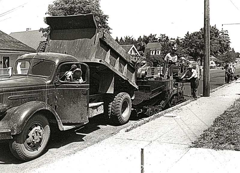 COURTESY OF CITY OF PORTLAND ARCHIVES - Here, a road crew was dumping and then laying asphalt on Woodstock Boulevard, somewhere between S.E. 52nd and 67th, in 1951. Unlike todays Portland work crews  with bright colored vests and safety hats and goggles, these workers wore cloth hats, and some not even wearing heavy duty work clothes or boots.