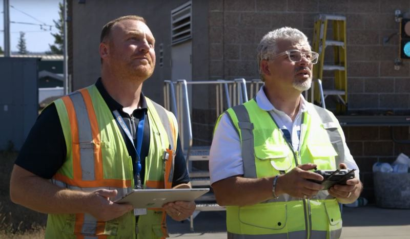 SCREENSHOT - Maintenance of Way Coordinator Matt Baccitich, left, watches as assistant manager of bus and rail operations Gregg Marshall pilots the agency's new drone.