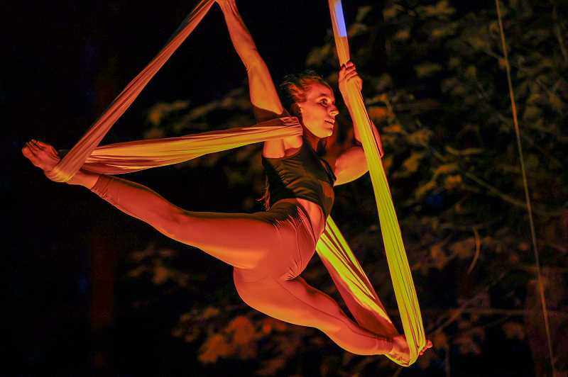 PMG PHOTO: JONATHAN VILLAGOMEZ - A-WOL aerialist Angela Bryant is suspended near the treetops in rehearsal for Art in the Dark at at Mary S. Young Park in West Linn.