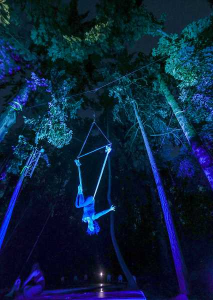 PMG PHOTO: JONATHAN VILLAGOMEZ - A-WOL aerialist Olivia Buss suspends herself up in the trees during a performance rehearsal of Art in the dark at Mary S. Young Park in West Linn. Buss says that if anything the show is about reconnection and trust.