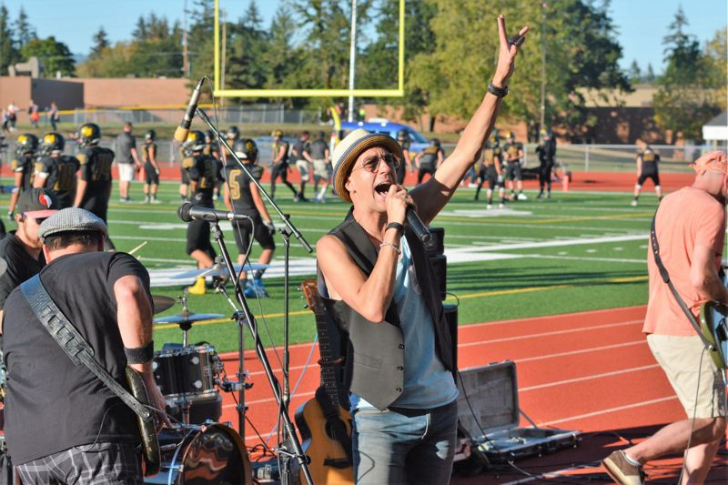 PMG FILE PHOTO - Lead singer Bart Hafeman, center, and Hit Machine, of Scappoose, perform at Doc Ackerson Stadium at St. Helens High School in 2016.