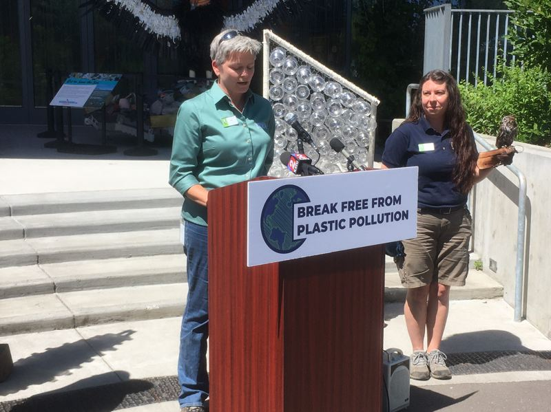 PMG PHOTO: PETER WONG - Amy Cutting, Oregon Zoo director of animal care and an animal curator, speaks at an event Friday, July 23, about plastics pollution and pending state and federal legislation, Behind her is a display of single-use plastic water bottles, which the zoo discontinued three years ago. Next to Cutting is Bree Boothe, who holds Pinecone, a rescued Western screech owl.