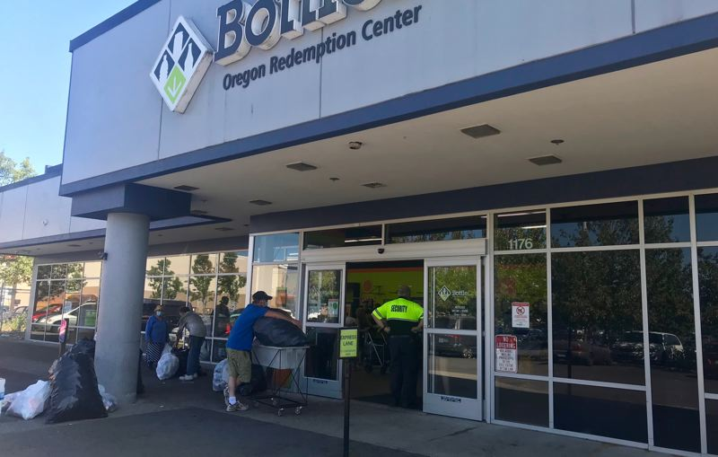 PMG PHOTO: ZANE SPARLING - An armed security guard stands in the doorway of an Oregon BottleDrop redemption center Friday, May 23.