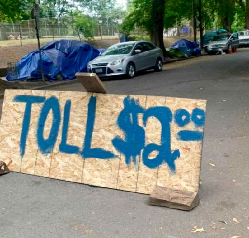 COURTESY: TJ BROWNING - A handmade sign describing Laurelhurst Park's nearby streets as 'toll roads' has made the round on Portland social media sites recently.