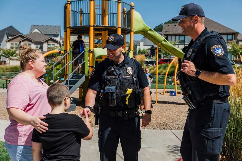 PMG FILE PHOTO - Tigard Police officers Brian Imus (center) and Jonathan Moehring (right), school resource officers in Tigard, chat with community members during a National Night Out block party.