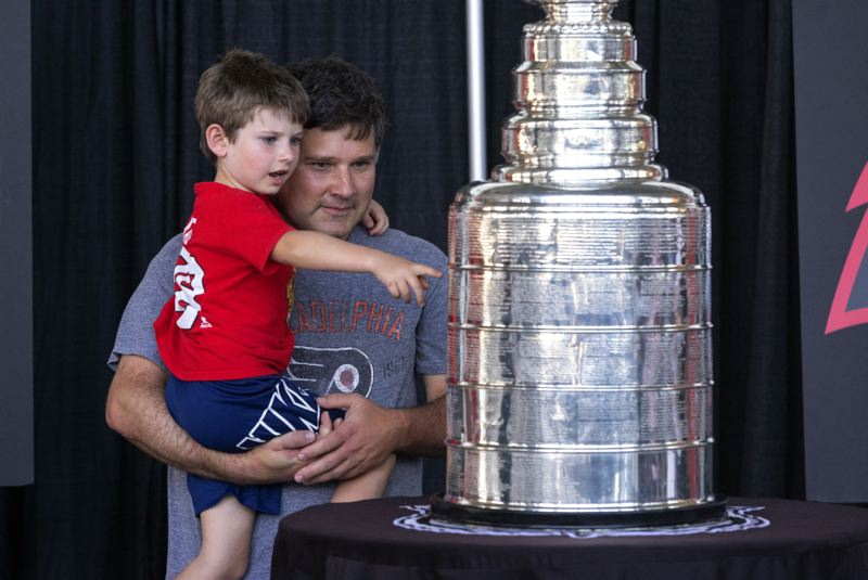 PMG PHOTO: JONATHAN HOUSE - Konrad Lasota and his son Kaden check out the Stanley Cup on Monday, July 26 at Veterans Memorial Coliseum.
