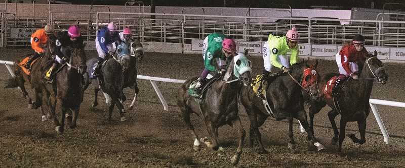 LON AUSTIN/CENTRAL OREGONIAN - Racers and their horses near the finish line on a Friday evening race on July 16.