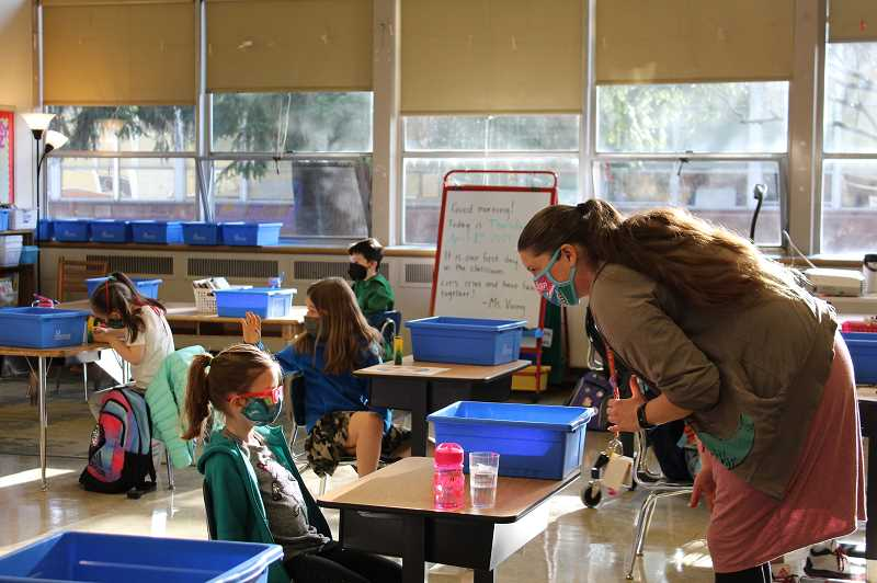 PMG PHOTO: JONATHAN HOUSE - Staff at Jason Lee Elementary School in Southeast Portland help first-grade students get settled during the first day back on campus in March 2021. Portland Public Schools will offer online learning for a limited number of students next year.