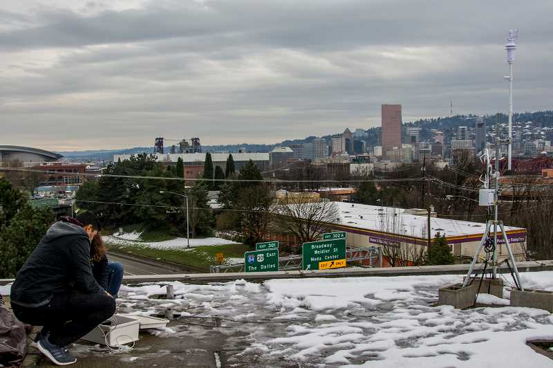 BETH CONYERS/PORTLAND PUBLIC SCHOOLS - An air quality team from Portland State University uses monitoring equipment atop the roof of Harriet Tubman Middle School in February 2018. Portland Public Schools says an I-5 freeway expansion project would require the school to be rebuilt nearby due to poor air quality.