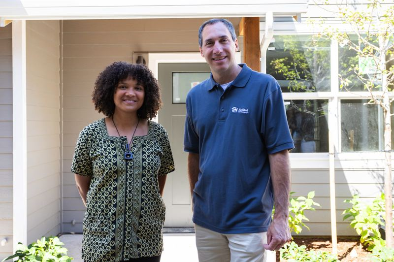 SUBMITTED PHOTO - Habitat for Humanity regional CEO, Steve Messinetti, right, poses for a photo with Jamie Hippe outside her new home in Portland's Cully neighborhood.