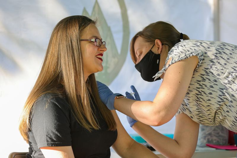PMG PHOTO: JONATHAN VILLAGOMEZ - The St. Helens'  concert series, 13 Nights on the River, also hosts on-site COVID-19 vaccinations. Nurse Practitioner Emily Paddon with Columbia Health Services is seen giving Victoria Lukomskiy her first dose of the Pfizer vaccine.,