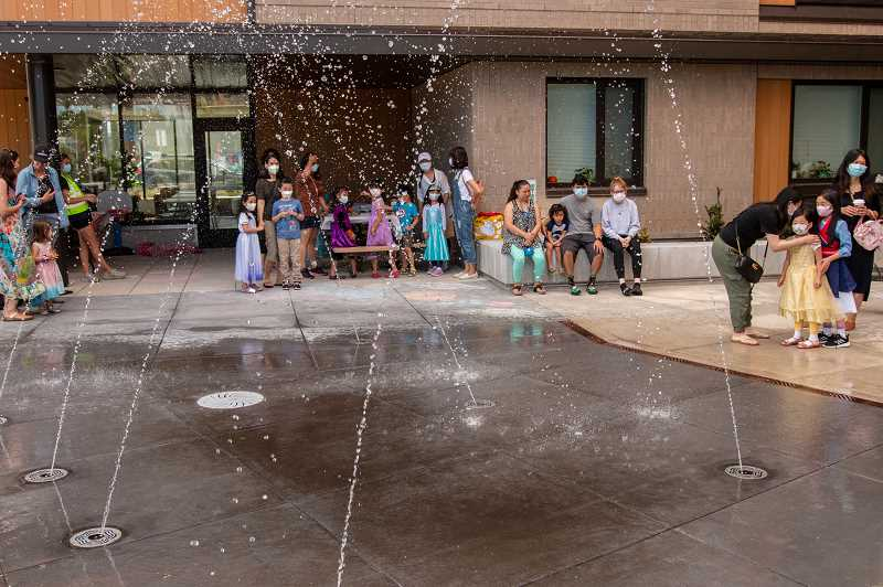 PMG PHOTO: KELCIE GREGA - Children hesitate before running through a splash pad at the Cedar Grove Apartments complex on Cornell Road in Beaverton on Tuesday, July 27 2021.