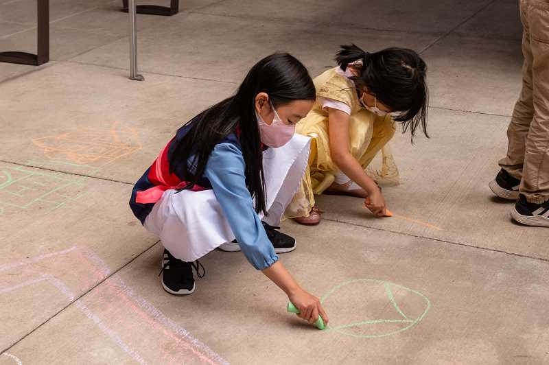 PMG PHOTO: KELCIE GREGA  - Children draw portraits with sidewalk chalk on the plaza at Cedar Grove Apartments on Cornell Road in Beaverton on Tuesday, July 27, 2021.