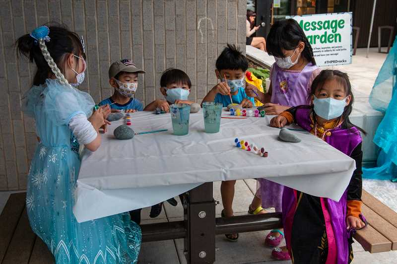 PMG PHOTO: KELCIE GREGA - Children paint on rocks during THPRD-sponsored 'Frozen in the Heat' event at Cedar Grove Apartments on Cornell Road on Tuesday, July 27, 2021.