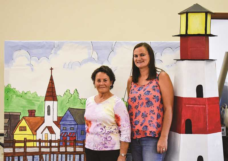 RAMONA MCCALLISTER - Patty Roberts, left, and Jenny Barker, pictured right, stand in front of their art work for the set of their VBS theme, which is Big Fish Bay. Roberts is the VBS leader for this summer, and Barker leads music for the week program. She is also wife of Pastor Daniel Barker.