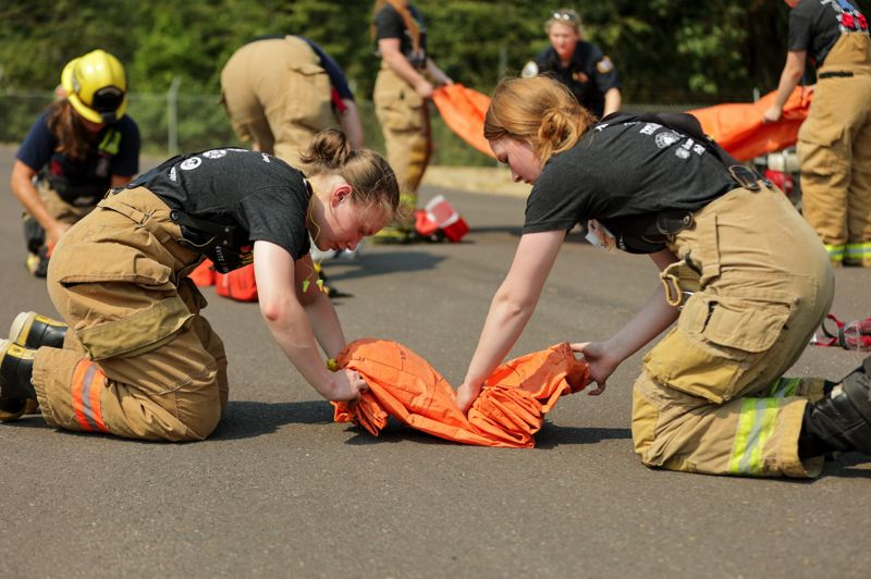 PMG PHOTO: JONATHAN VILLAGOMEZ - Sofia Sorokina (left) and Sydney Sims (right) wrap up their 'smokey packs' in an exercise at the Tualatin Valley Fire & Rescue training facility in Sherwood.
