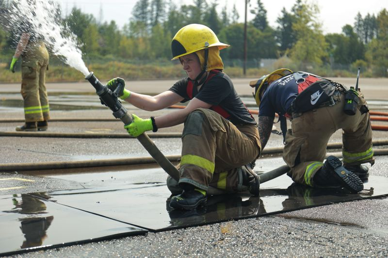 PMG PHOTO: JONATHAN VILLAGOMEZ - Kylah Hansen uses a fire hose during her first day of Metro Fire Camp training on July 30.