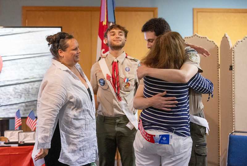PMG PHOTO: JONATHAN HOUSE - The new Eagle Scouts hug their mothers during the ceremony on Monday.