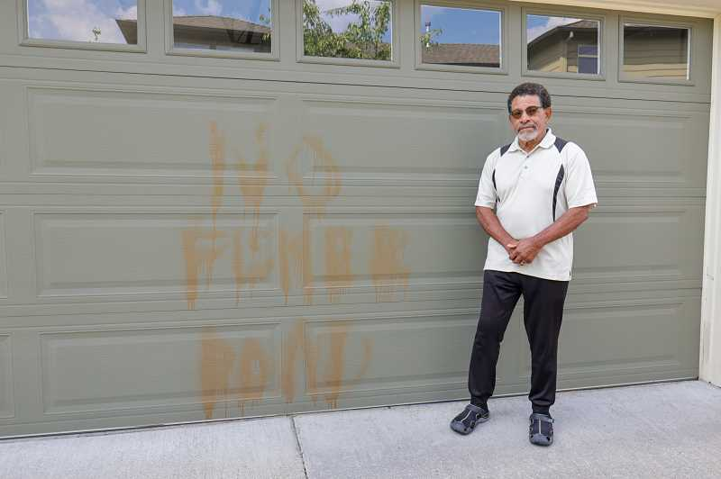 PMG PHOTO: JONATHAN VILLAGOMEZ  - Mayor Ken Gibson shows where someone vandalized his garage door with spray paint last week, apparently protesting the proposed extension of Southwest Fischer Road. Gibson lives in the Edgewater community.