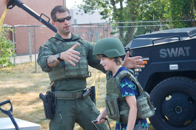 PMG PHOTO: CHRISTOPHER KEIZUR - Gresham Officer Ryan Rasmussen showed off his gear to kids during a National Night Out event Tuesday, Aug. 3, in the Arts Plaza.