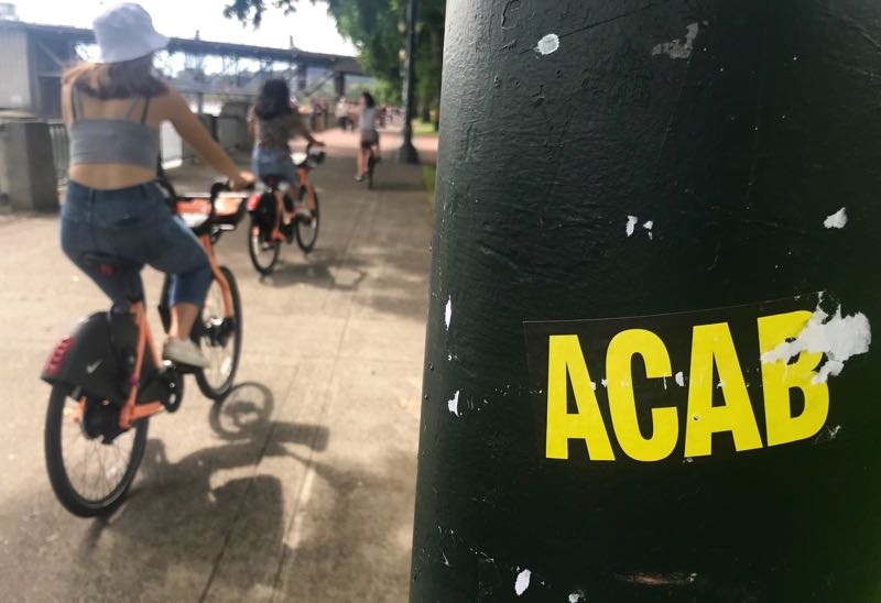 PMG PHOTO: ZANE SPARLING - A sticker displaying an Antifa slogan was plastered on a lamppost in Tom McCall Waterfront Park on Saturday, Aug. 7 in Portland.