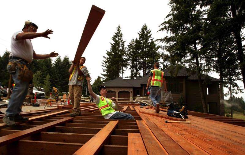 L.E. BASKOW / PORTLAND TRIBUNE - 06/27/2007 -  (LtoR) Ken Walker with the Northwest College of Construction teams up with YouthBuilders Josh Best, Sean Hull and Jeremy Poland to complete an entertainment deck for the soon to open Street of Dreams in Clackamas County.KEYWORDS: Oregon City, homes, teens, construction, Marklund