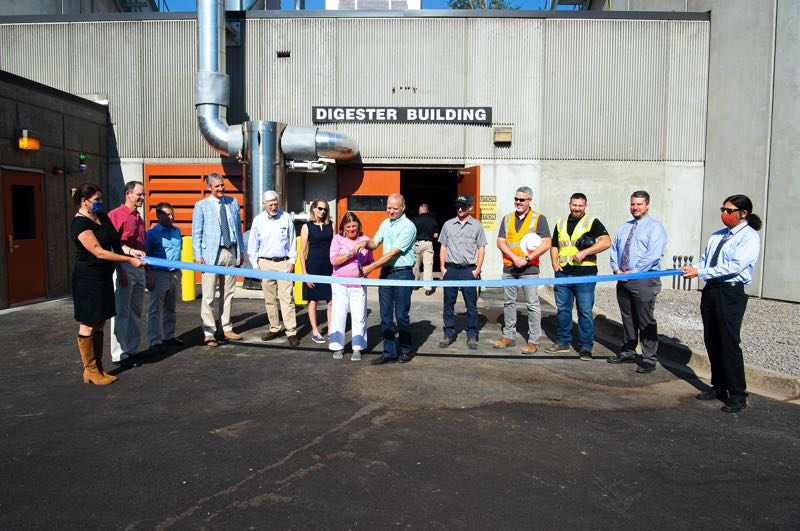 COURTESY PHOTO: WATER ENVIRONMENT SERVICES - Clackamas County Commissioner Martha Schrader cuts a ceremonial ribbon at Wednesday's unveiling ceremony, standing next to Commissioner Paul Savas and representatives from WES, ETO and PGE.