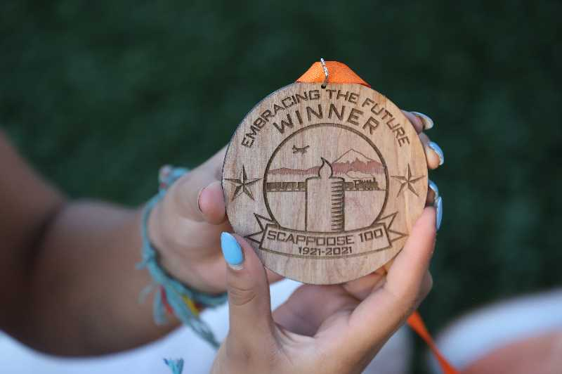 COURTESY PHOTO: JENNIFER KOMP - A player holds the wood medal given to the winners of the Scappoose Centennial softball tournment.