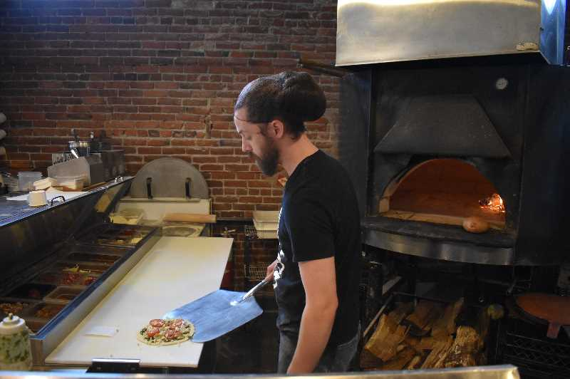 PMG PHOTO: RAYMOND RENDLEMAN - Clint McGhee, an employee of Mi Famiglia Wood Oven Pizzeria, enjoys his last day of working in the heat without having to wear a mask.