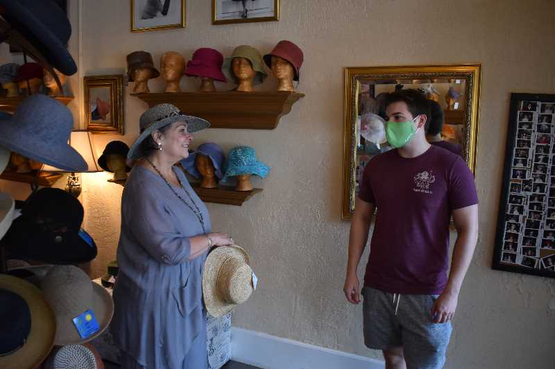 PMG PHOTO: RAYMOND RENDLEMAN - You Can Leave Your Hat On owner Sandra Gillman helps Stuart Allen find a hat on Aug. 12.