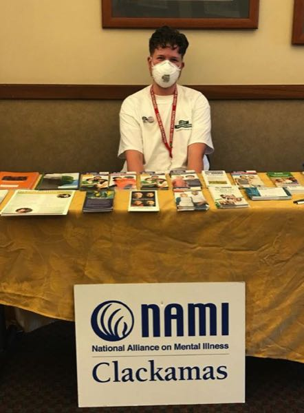 PMG PHOTO: LAURA CANIDA - Max Day, peer resource coordinator with NAMI Clackamas, answers questions and provides information to clients at a recent event.
