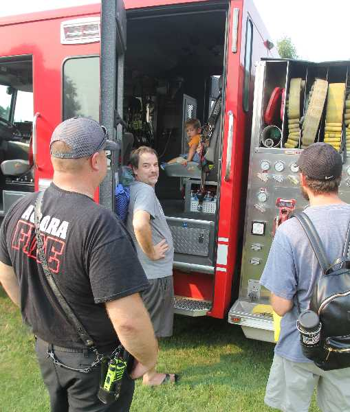 PMG PHOTO: JUSTIN MUCH - A firefighters view: Getting to climb into the Aurora Fire District vehicles was a popular attraction at the community celebration Saturday, Aug. 14.