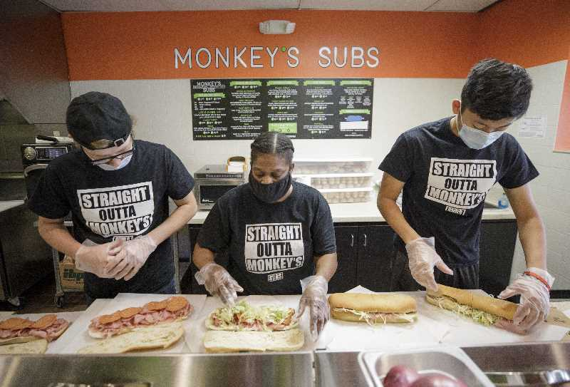 PMG PHOTO: JONATHAN HOUSE - Tricia Griffin, center, helps fulfill a large order of sub sandwiches at Monkey's Subs along with David Studer, left, and Bishan Zheng.