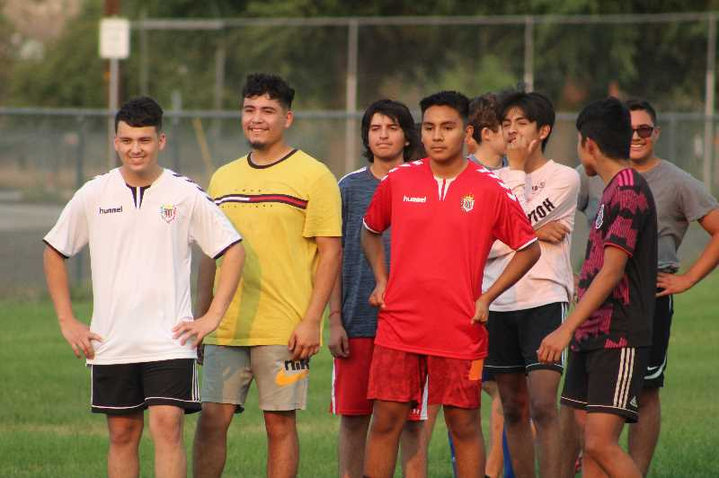 ANDY DIECKHOFF/MADRAS PIONEER - Some members of the Madras high school boys' soccer squad watch their teammates take part in a drill.