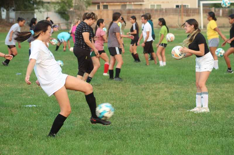 ANDY DIECKHOFF/MADRAS PIONEER - The Madras High School girls' soccer team kicked things off with some passing drills.