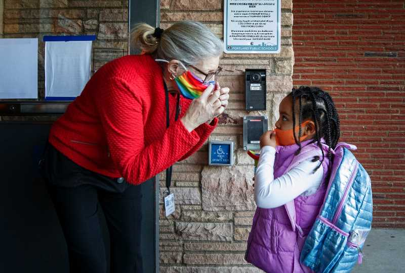 PMG PHOTO: JONATHAN HOUSE - Jason Lee Elementary School substitute teacher Sarah Lewins helps Mintwob Mintwab properly put on her mask at the start of the first day of in-person, hybrid learning in spring 2021. Portland Public Schools announced all staff will be required to be vaccinated before the start of the 2021-22 school year.