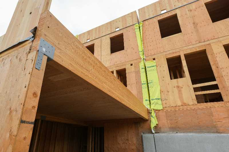 PMG PHOTO: JONATHAN VILLAGOMEZ - A garage space at the Wilson Forest Park Townhomes in Northwest Portland, with a large deck above it. The cross-laminated timber townhomes are deliberately kept four and a half inches apart (at the yellow fireproofing film) so that they can't be considered condominiums.