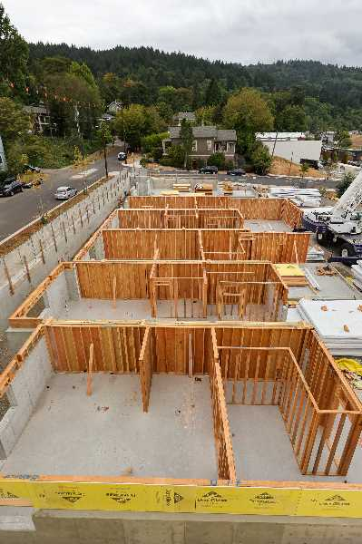 PMG PHOTO: JONATHAN VILLAGOMEZ - Some of the Wilson Forest Park Townhomes in Northwest Portland that have yet to reach full height. Forest Park is in the background..