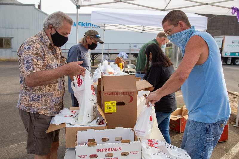 COURTESY PHOTO: MARION POLK FOOD SHARE - Volunteers Mike, foreground left, and Doug, foreground right, package fresh food items during a distribution at AWARE Food Bank in Woodburn