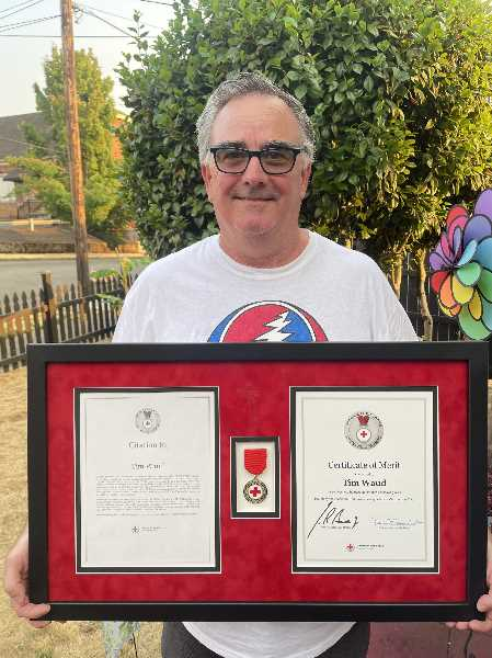 PHOTO COURTESY: TIM WAUD - Oregon City's Tim Waud poses with the highest award given by the Red Cross to an individual who helps save a life using knowledge from a training course.